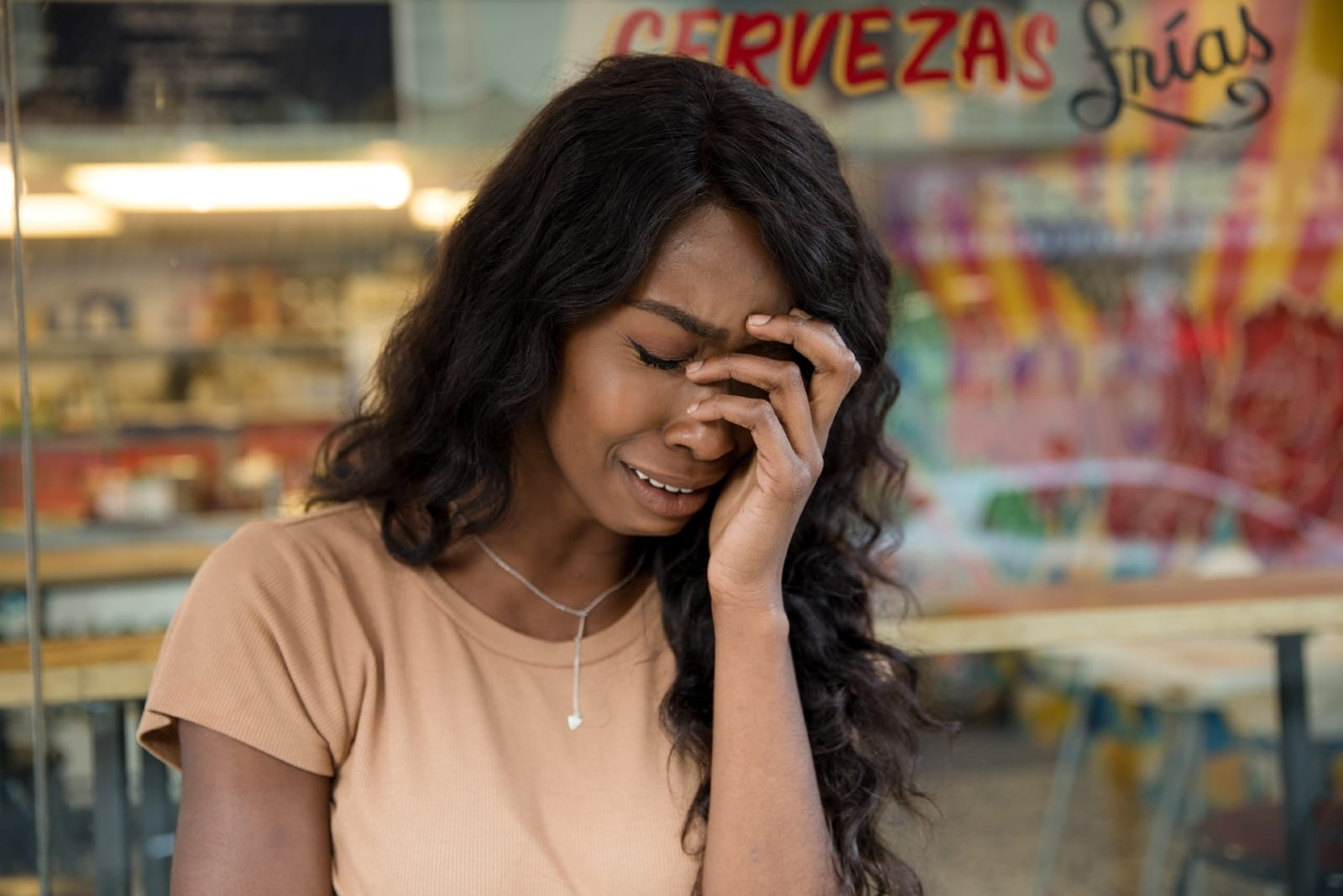 woman crying while standing near storefront
