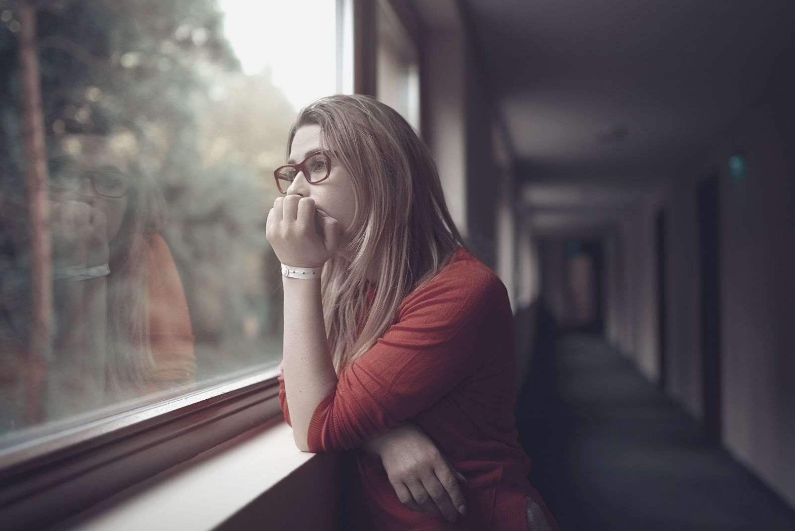 woman deeply thinking leaning on the window sill looking outside