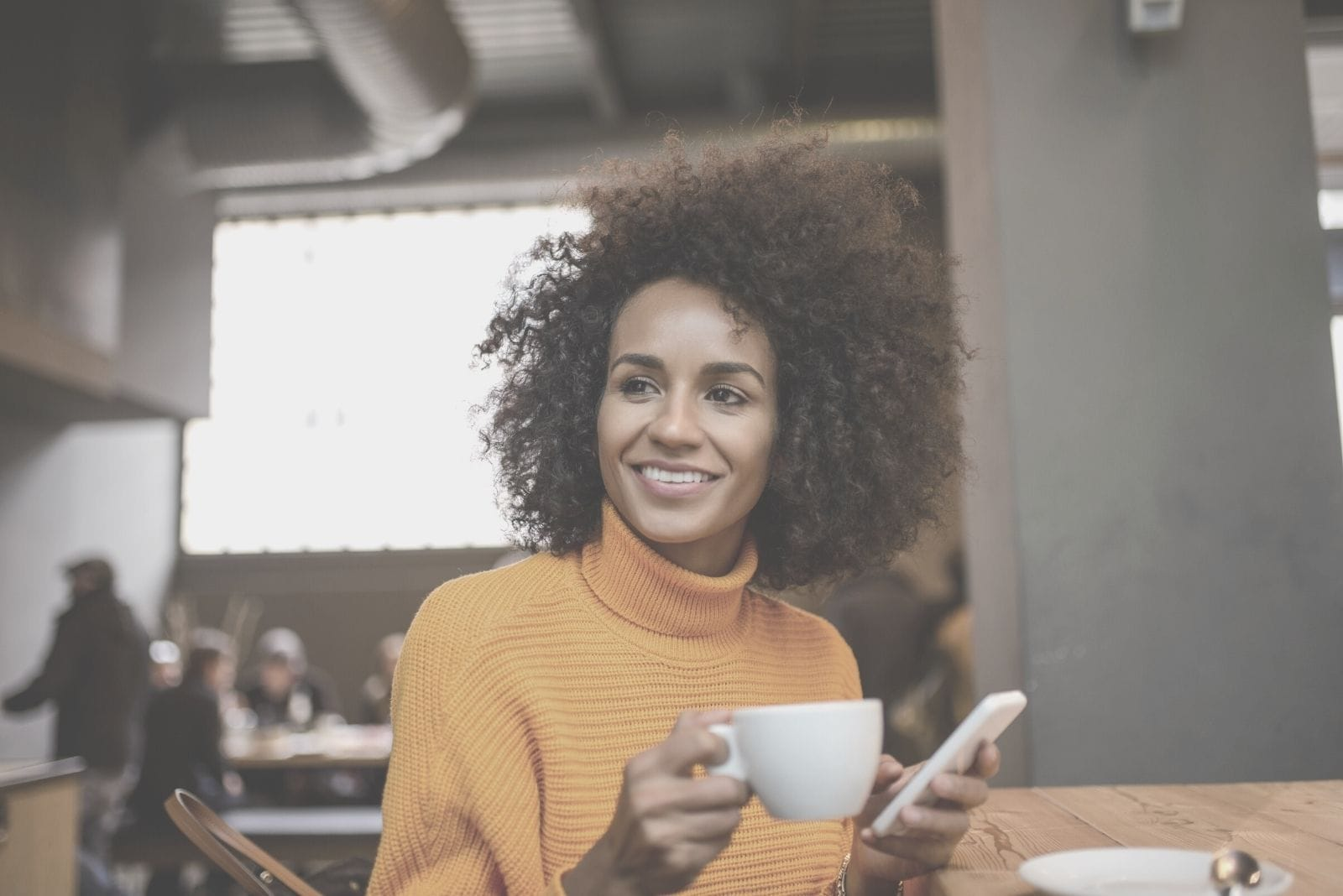 woman drinking coffee inside a cafe and holding a cellphone looking away and smiling
