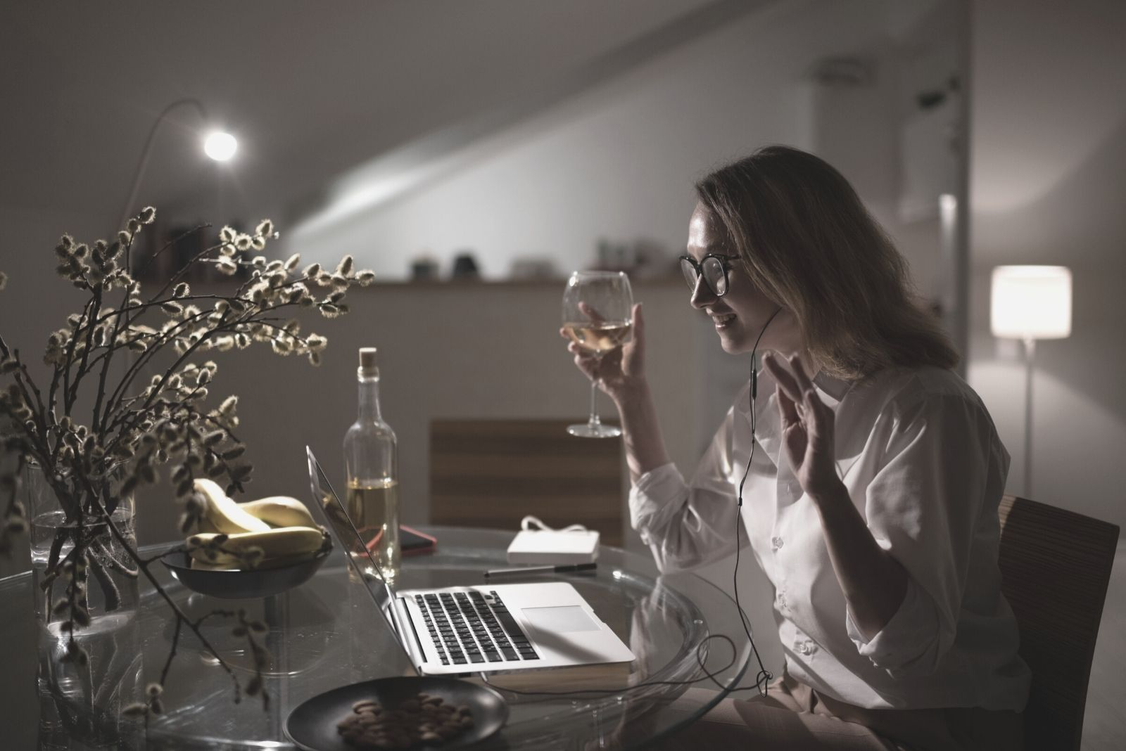 woman having a drink wine while chatting on the laptop during the night