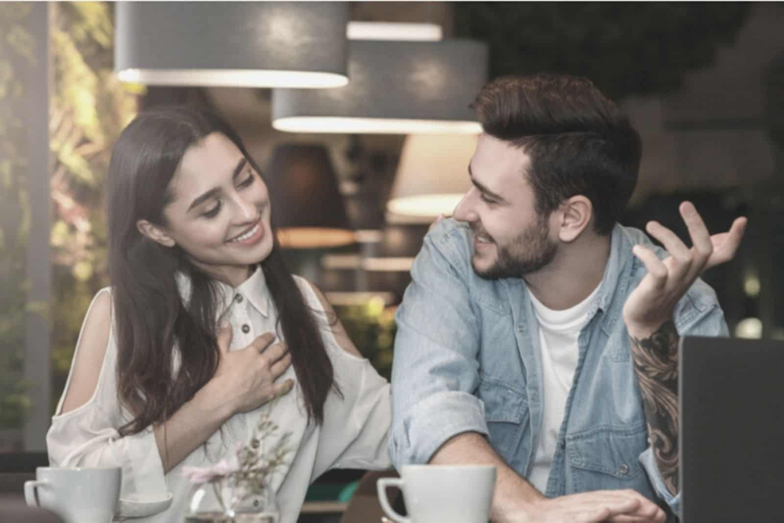 woman holding her chest and smiling while talking to a man beside her inside the cafe