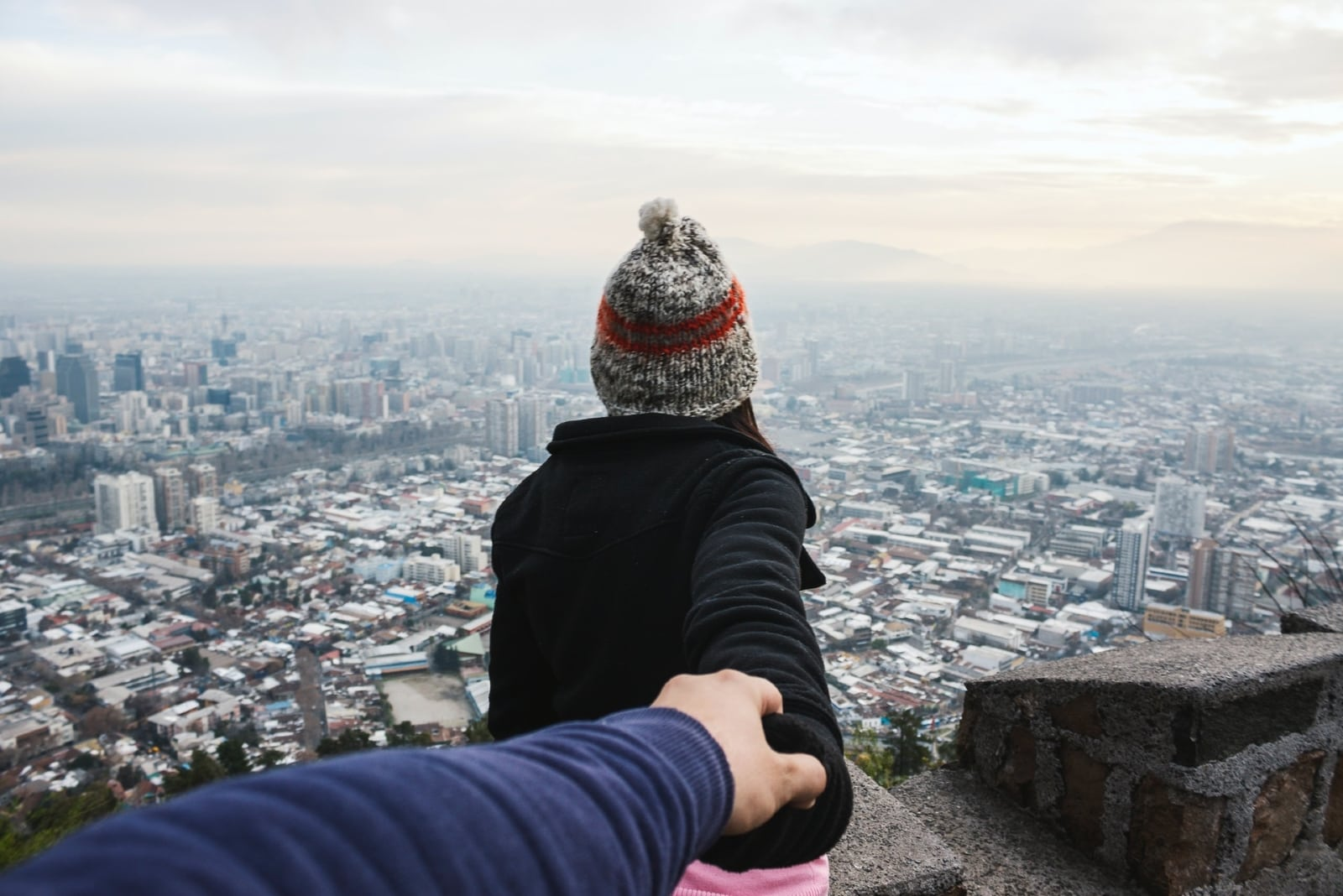 woman holding man's hand while looking at city