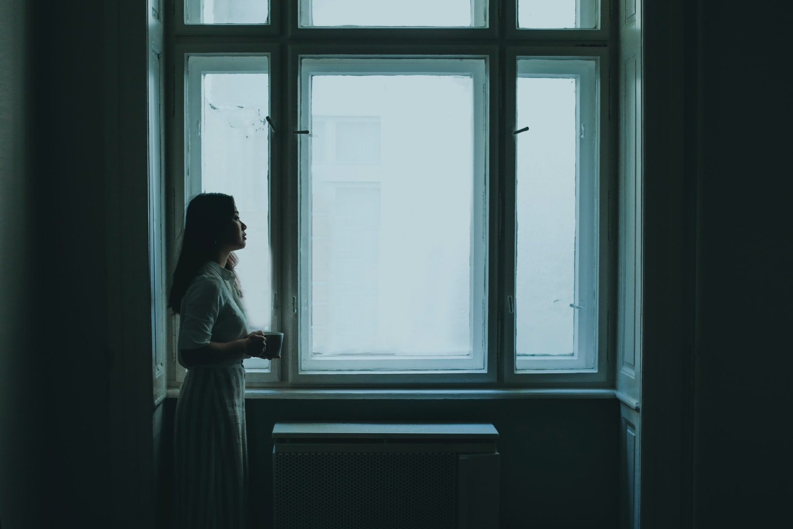 woman holding mug while standing near window