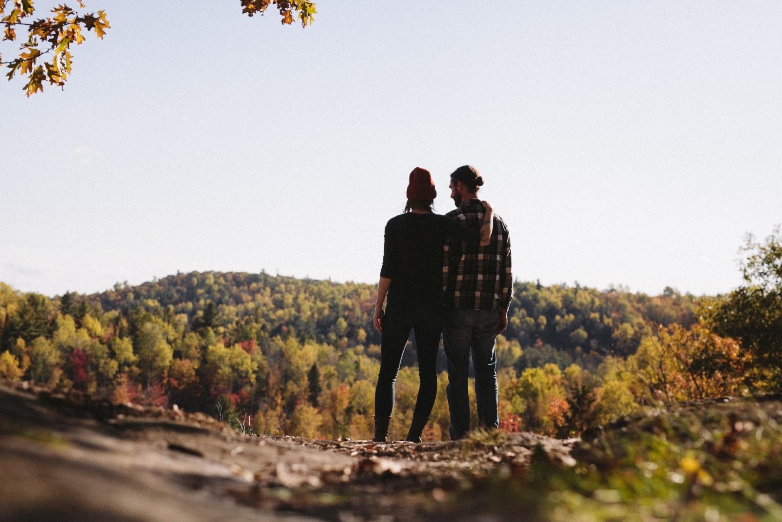 woman hugging man while standing near green grass field