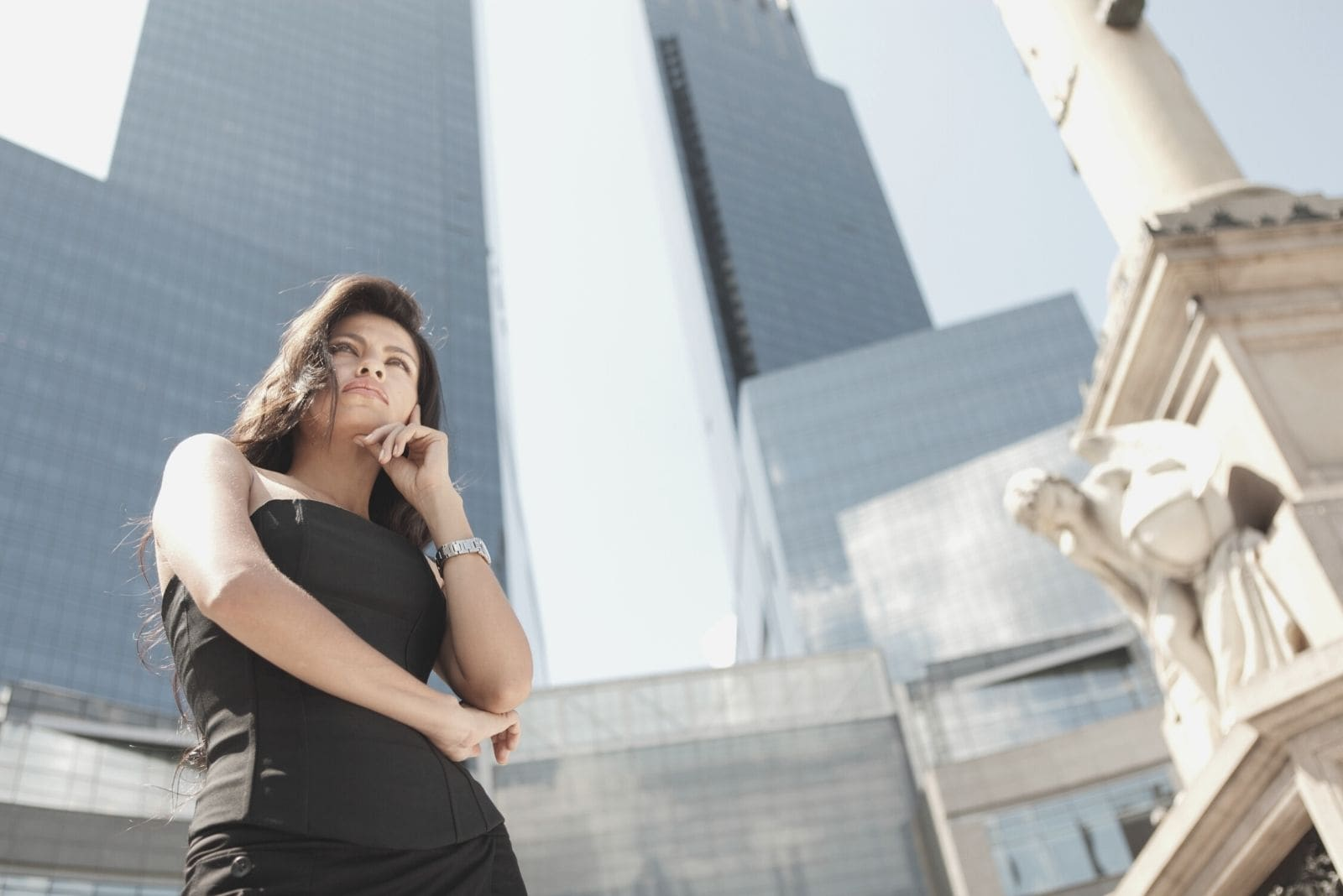 woman in black dress standing near the skyscrapers thinking in low angle