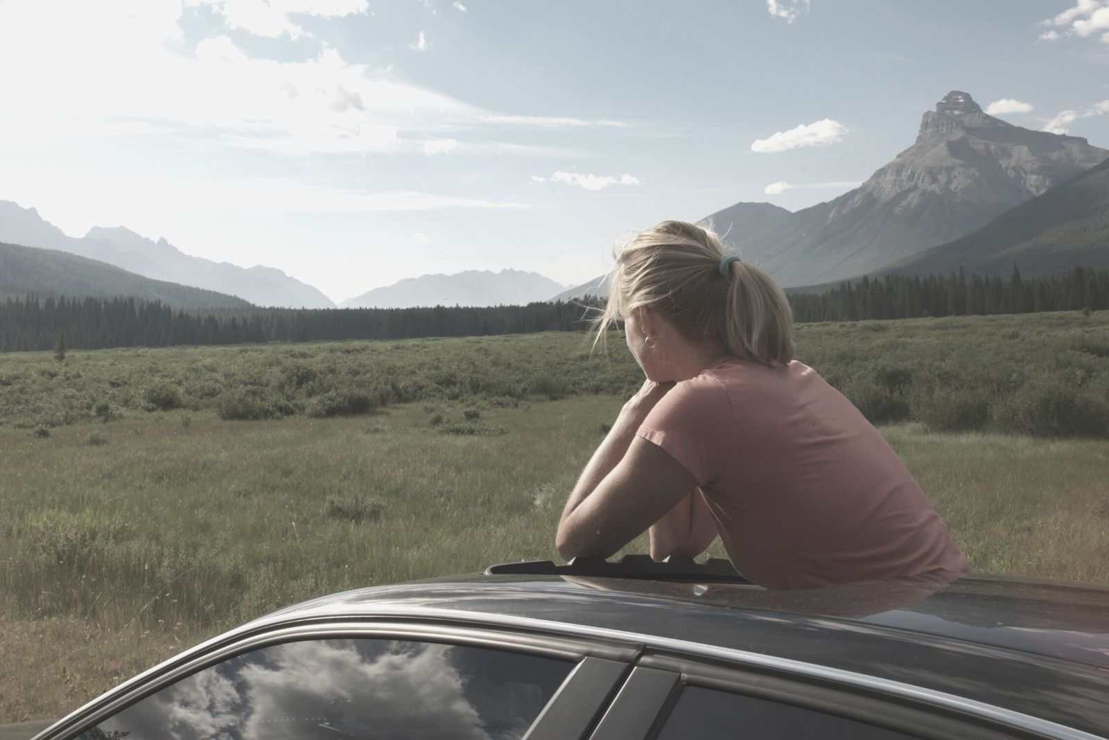 woman in the car looking outside in the meadow