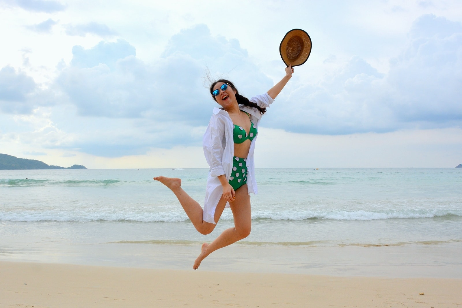 woman holding hat while jumping on seashore