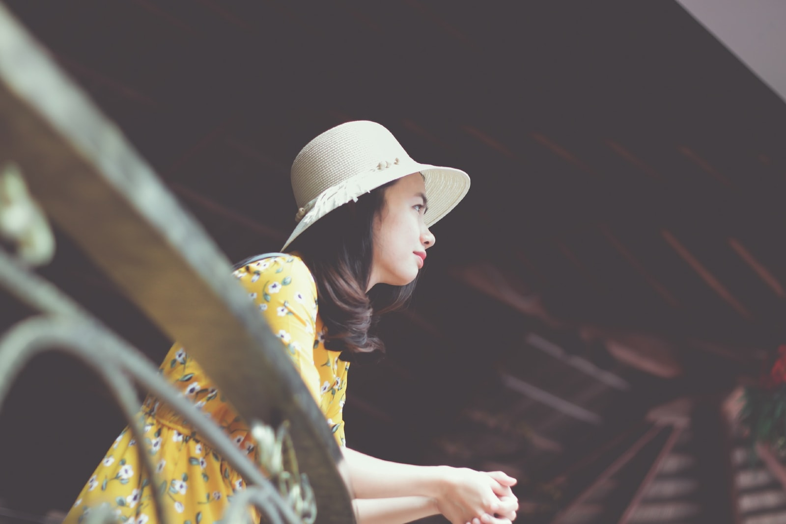 woman with hat leaning on metal fence