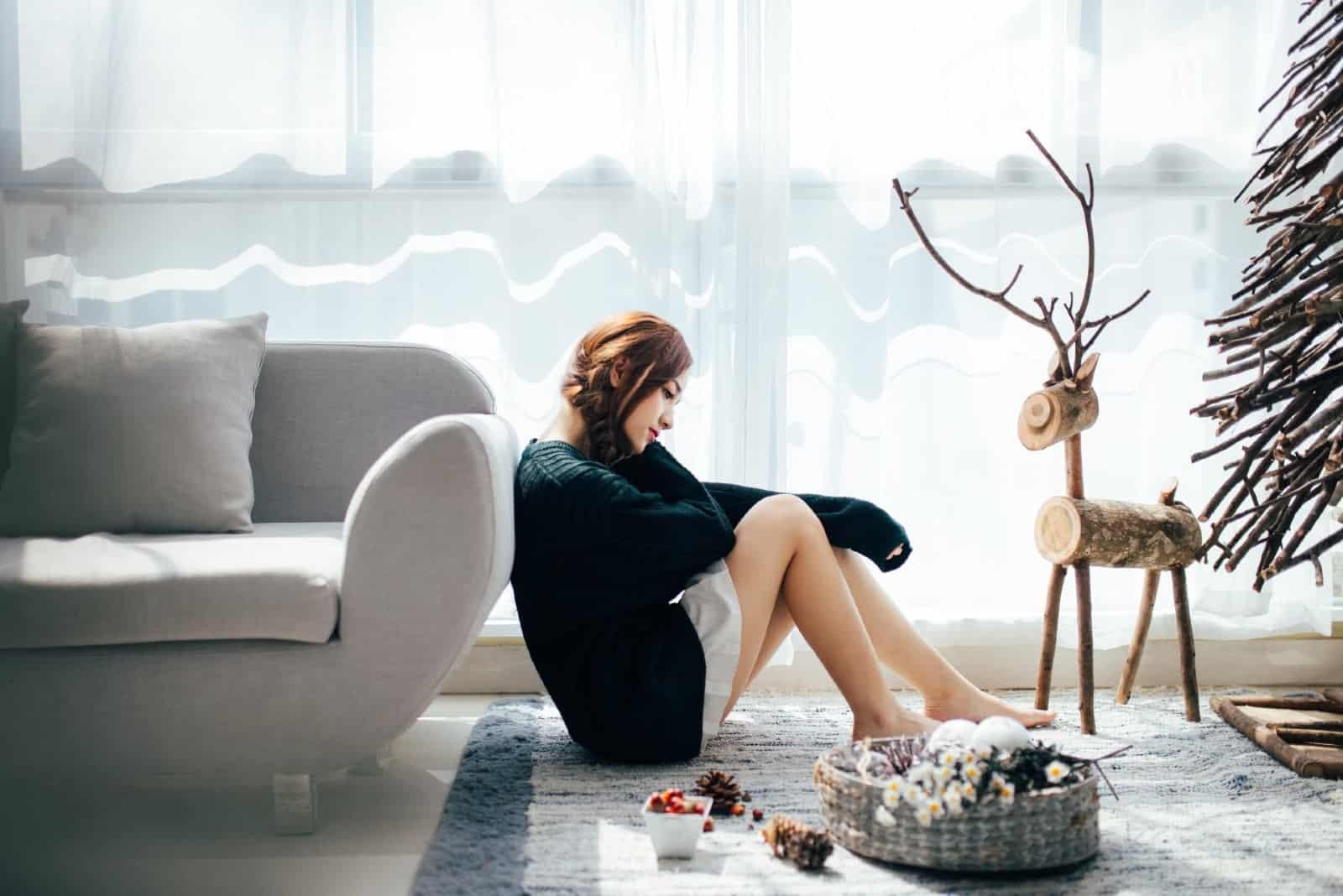 sad woman leaning on sofa while sitting on carpet