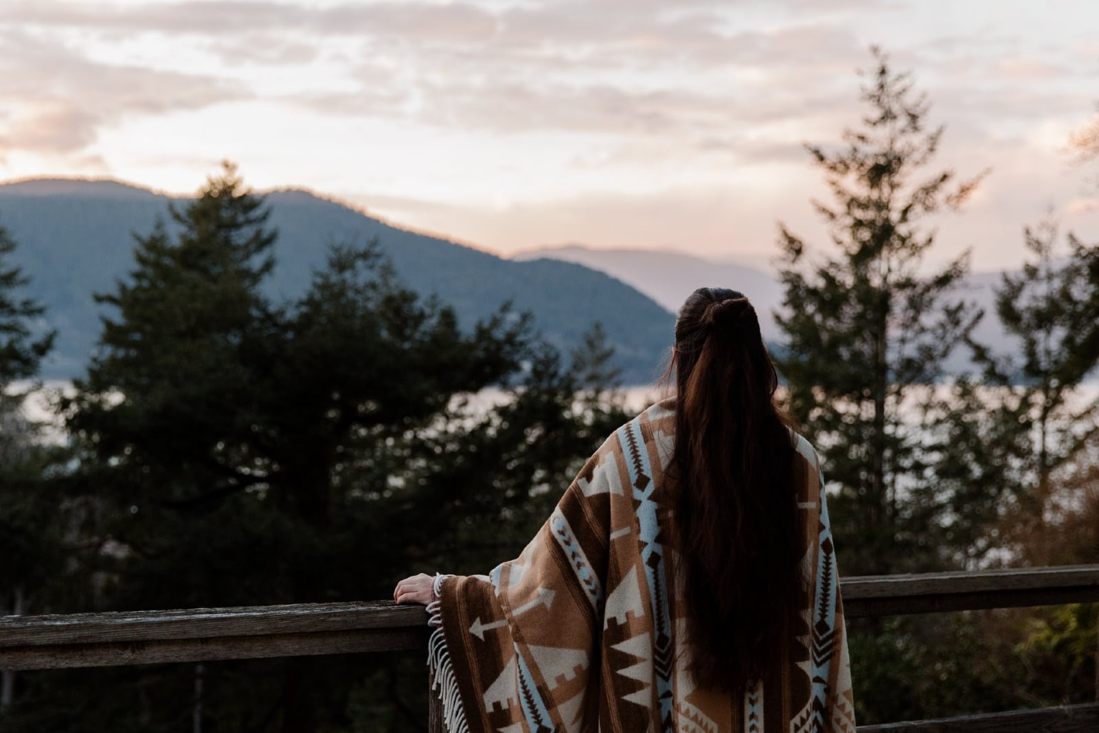 woman looking at mountain while standing on terrace