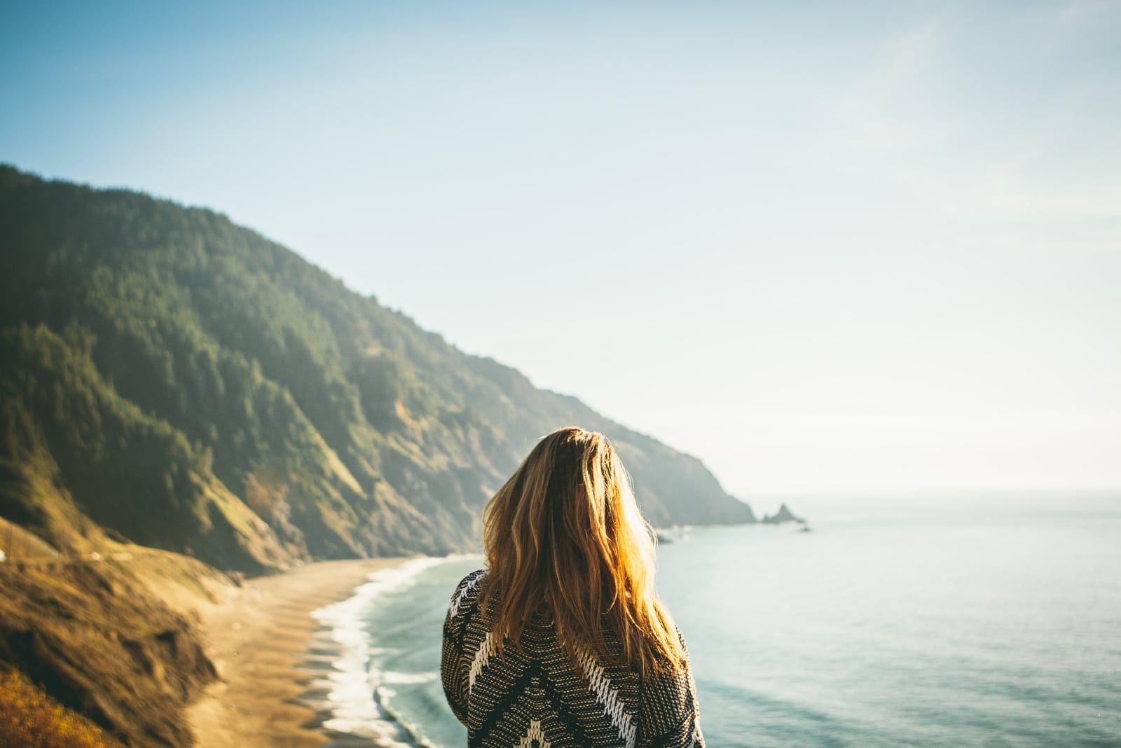 woman in gray sweater looking at ocean