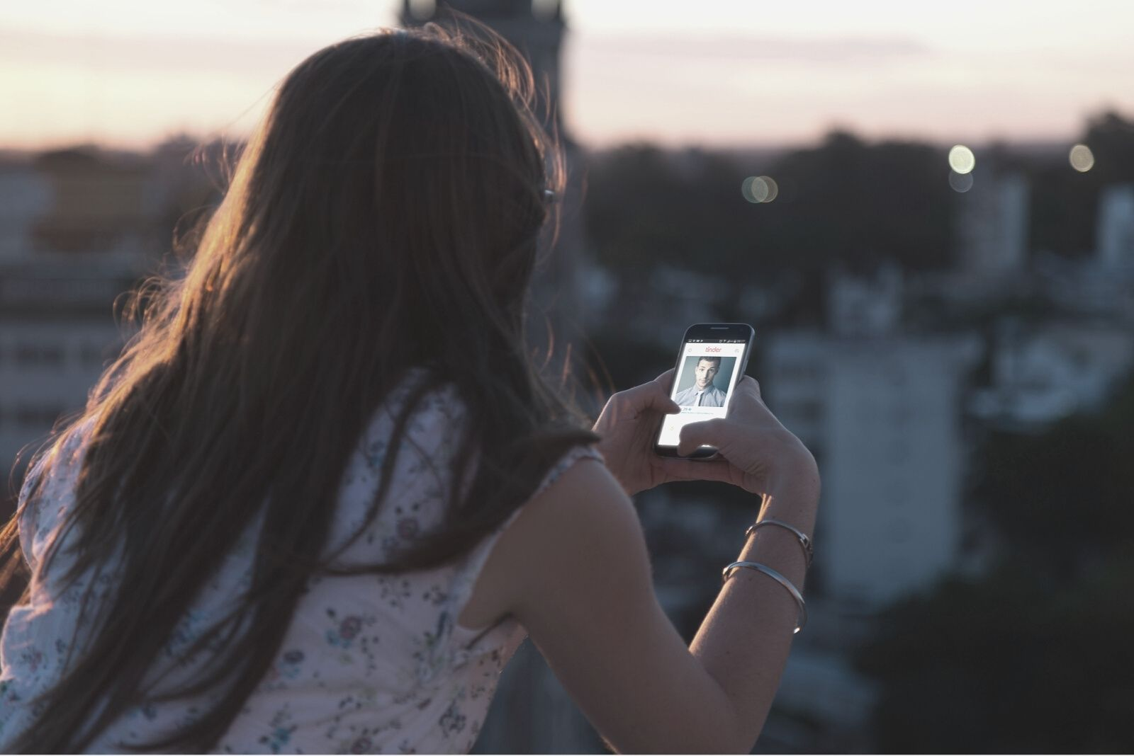 woman looking at picture of a man in her phone standing at rooftop