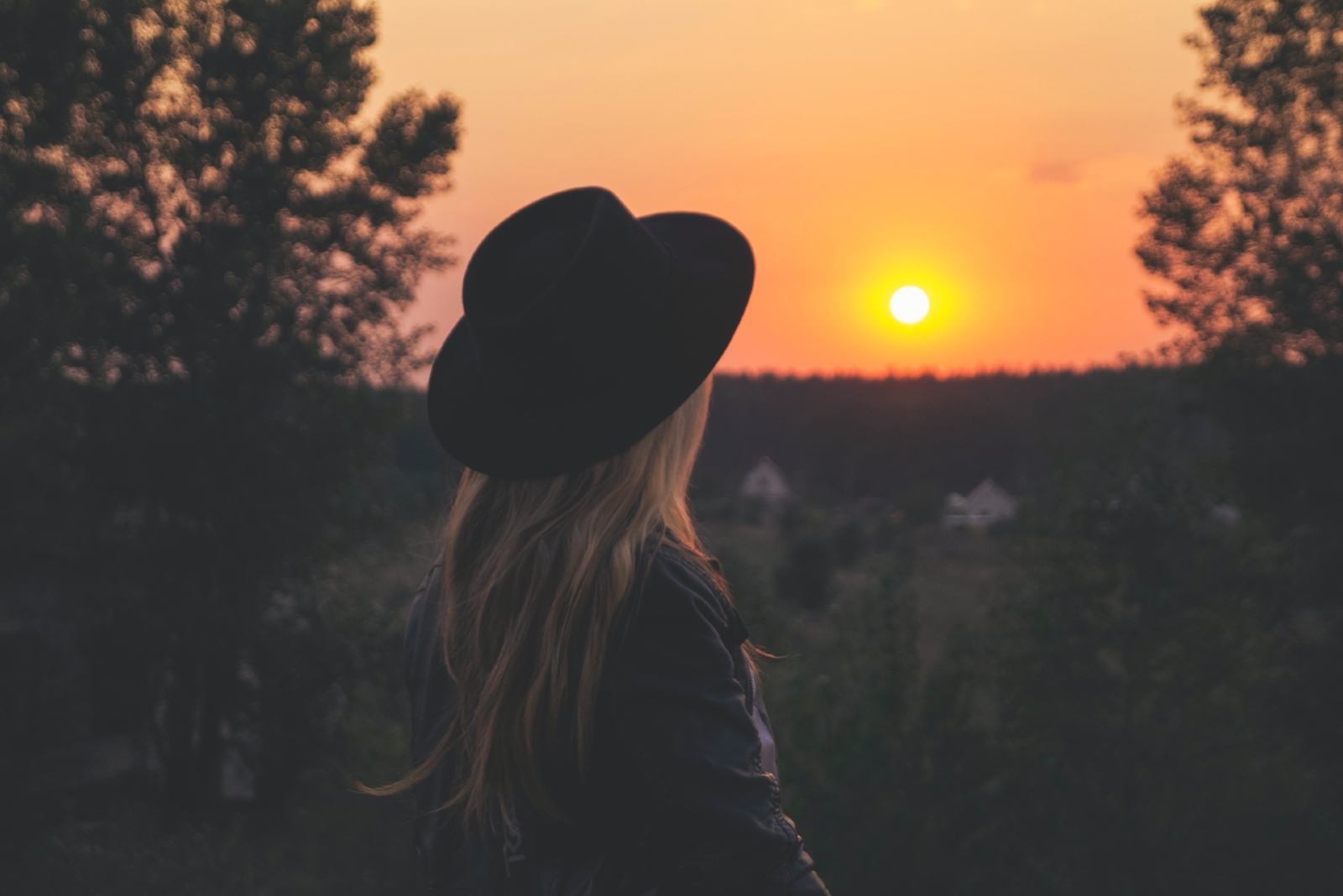woman with black hat looking at sunset