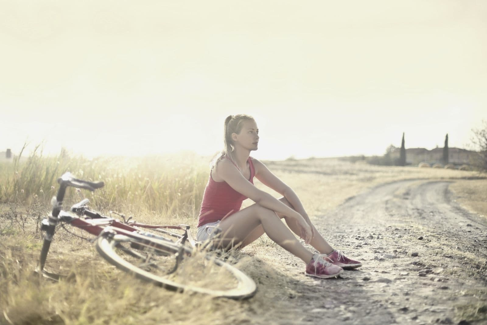 woman on dirtbike resting on the side on an open field of the country