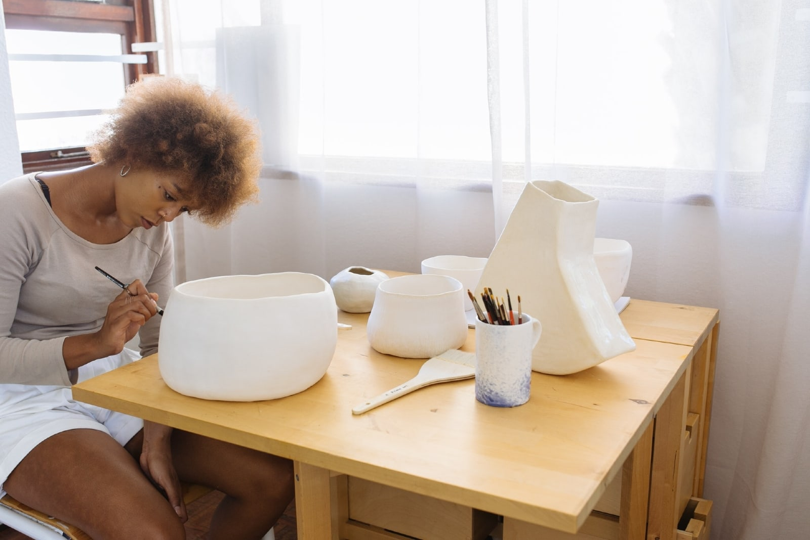 woman painting ceramic bowl while sitting at table