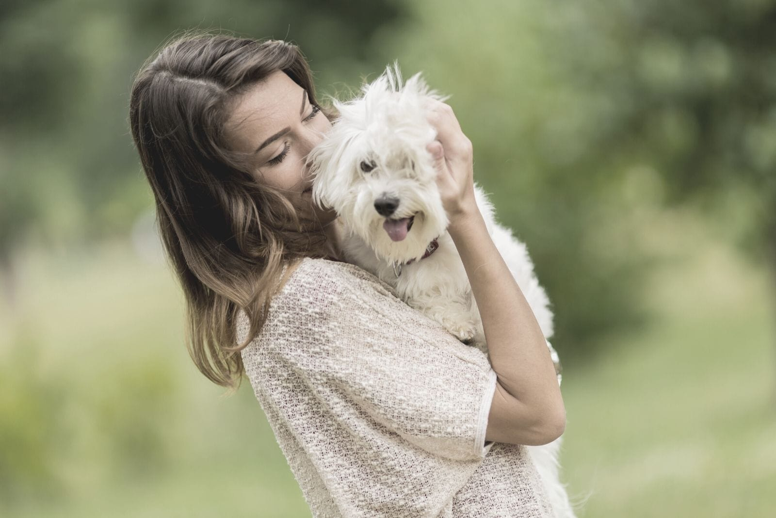 woman playing with a dog of maltese breed outdoors