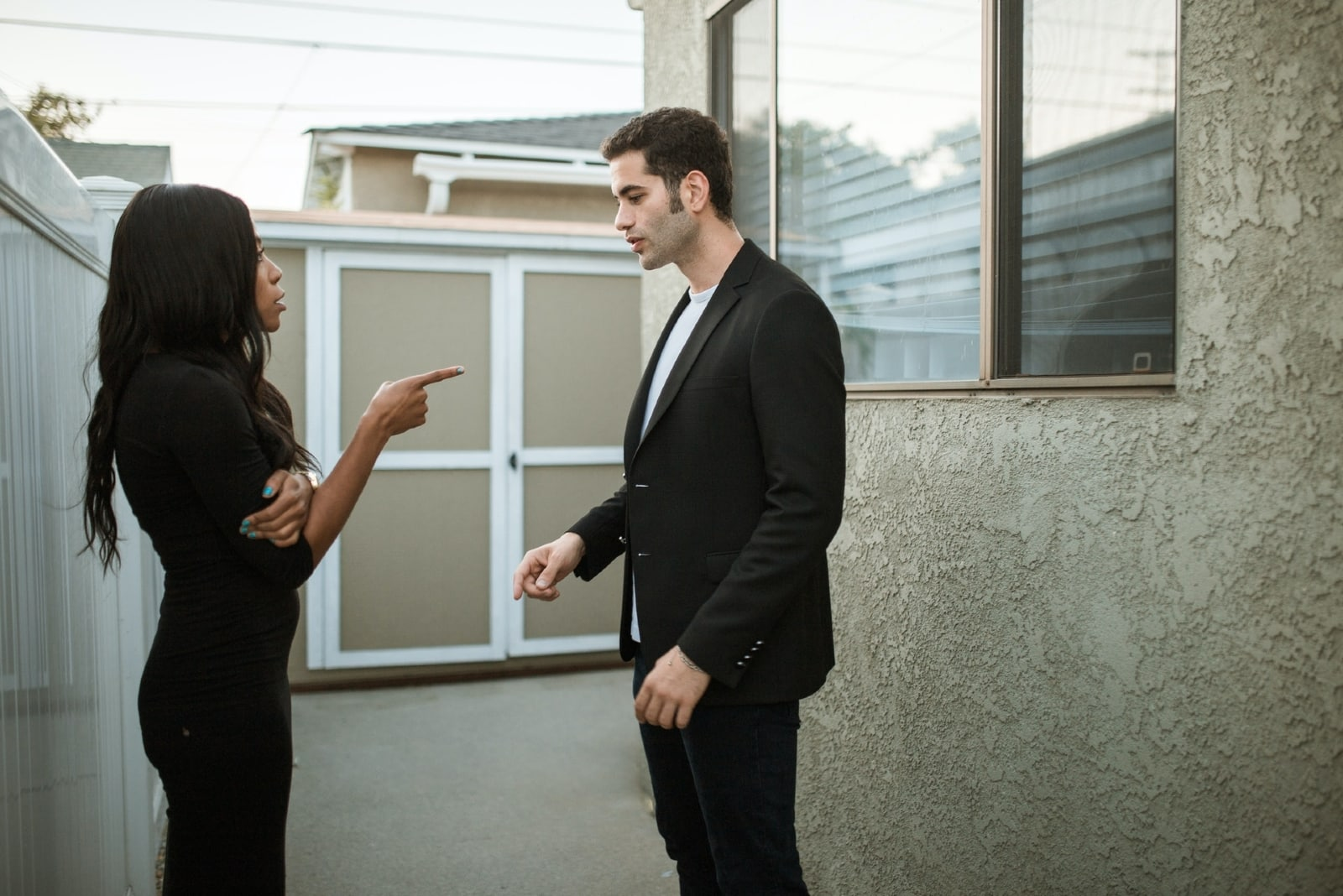 woman in black dress pointing finger at man