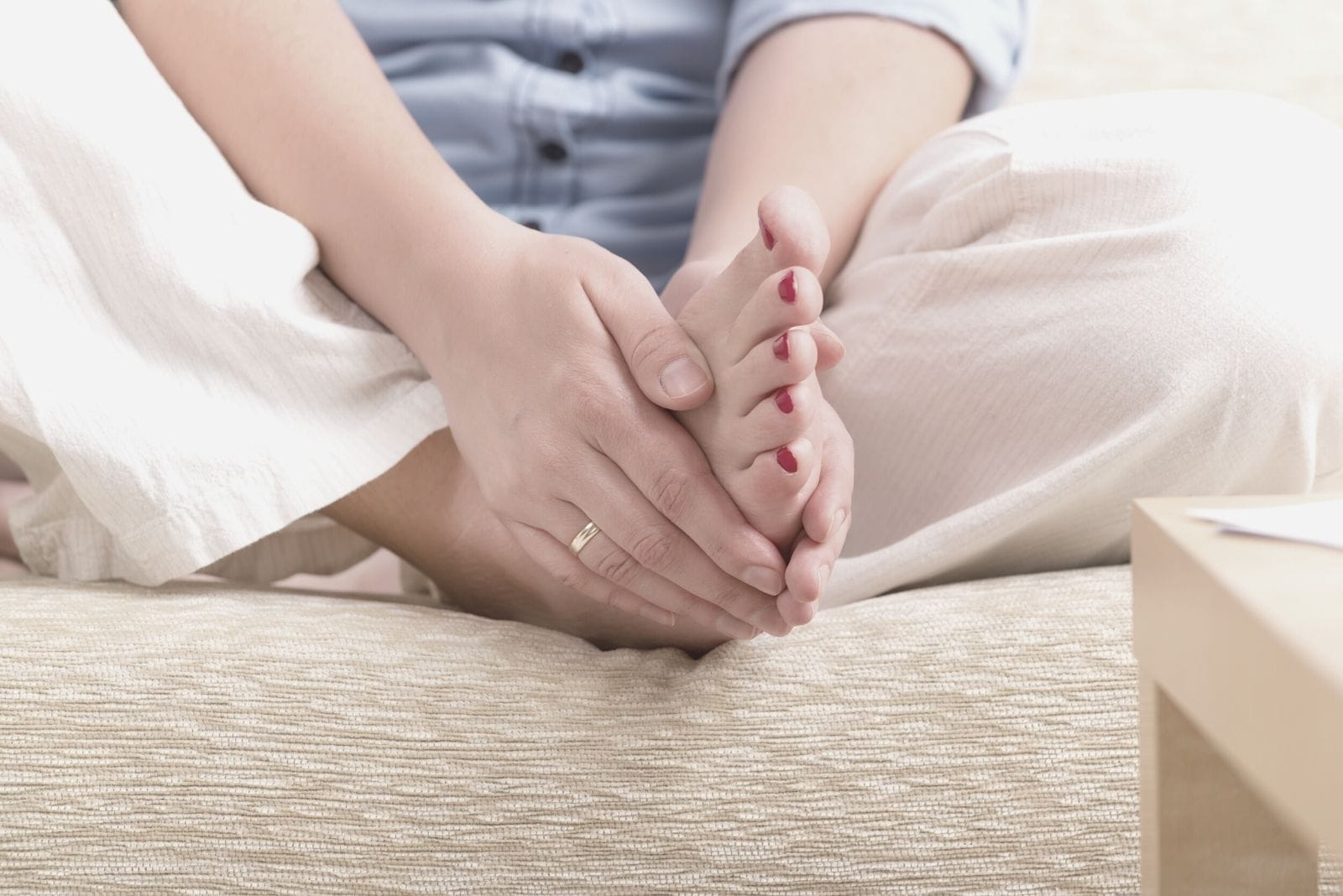 woman practicing self reiki transferring energy from the palm to the foot