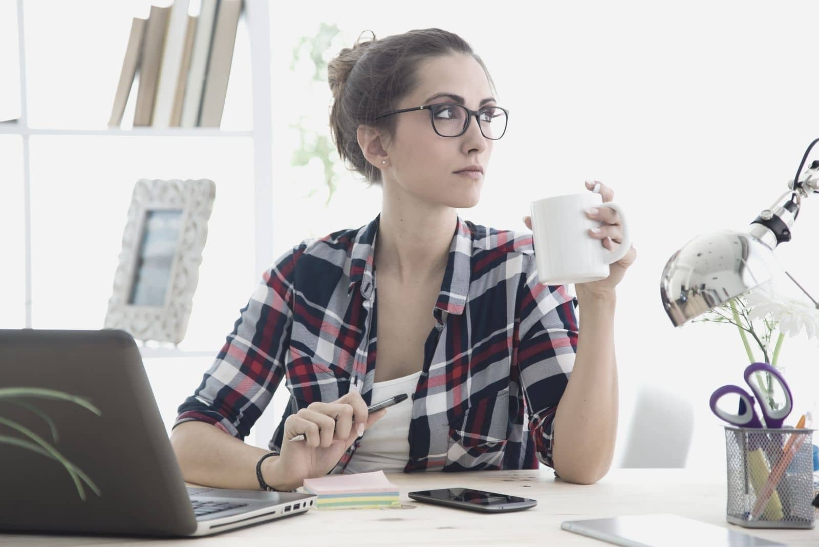 woman sitting in office thinking and looking away wearing eyeglasses and drinking from a mug