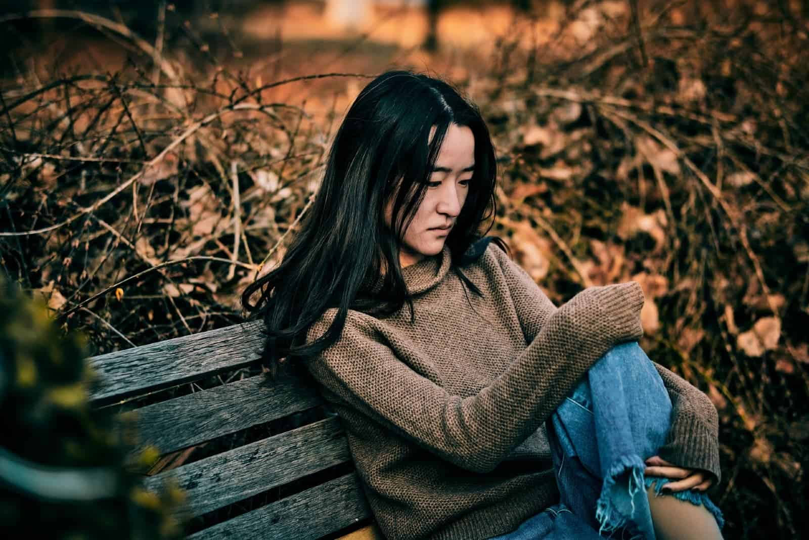 sad woman in brown sweater sitting on bench