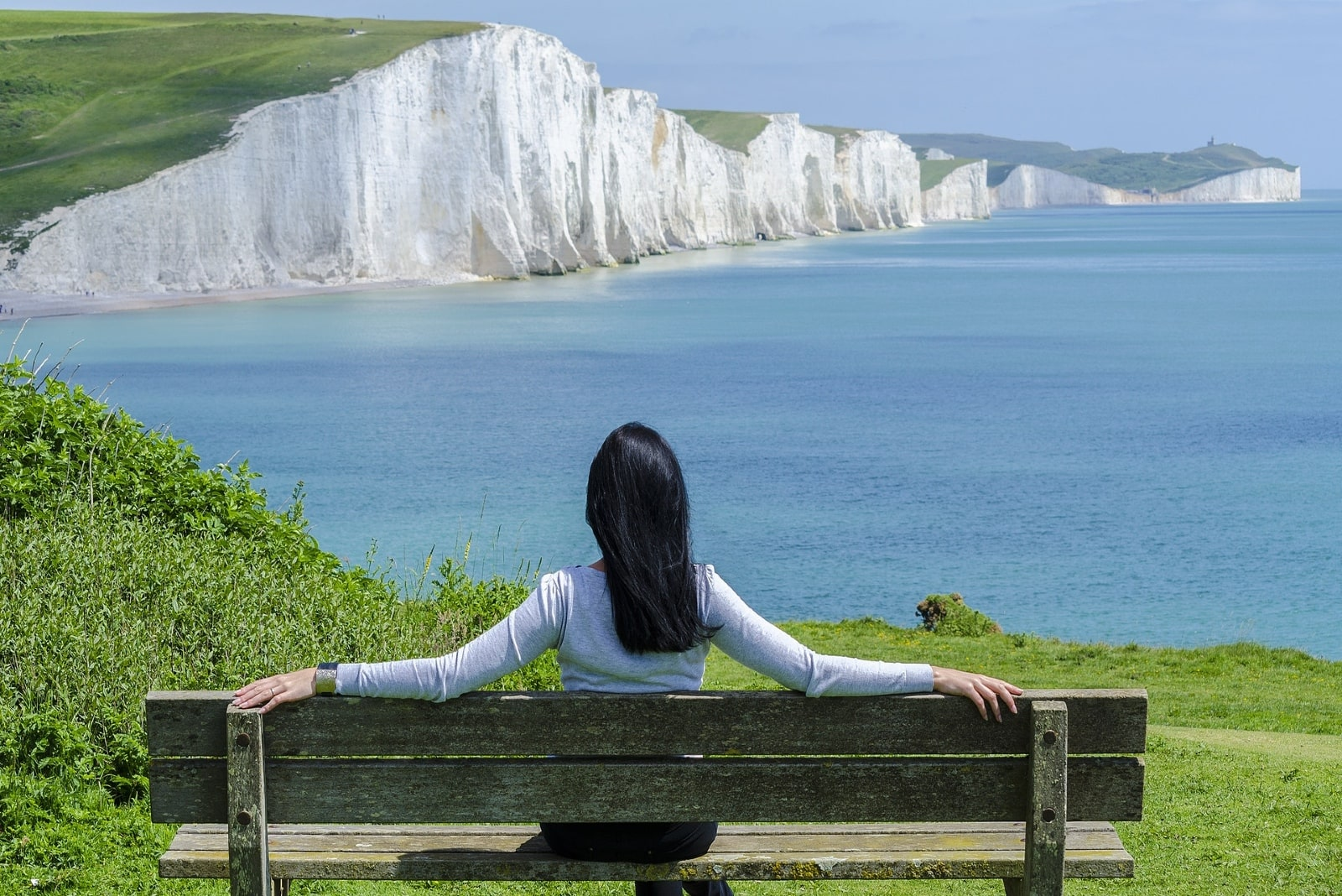 woman sitting on bench looking at ocean
