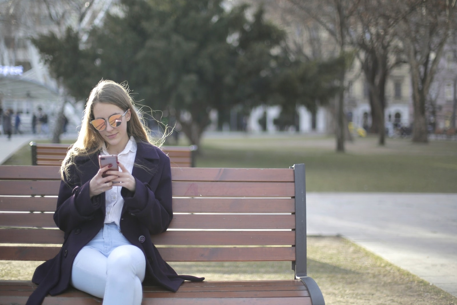 woman with sunglasses using smartphone while sitting on bench