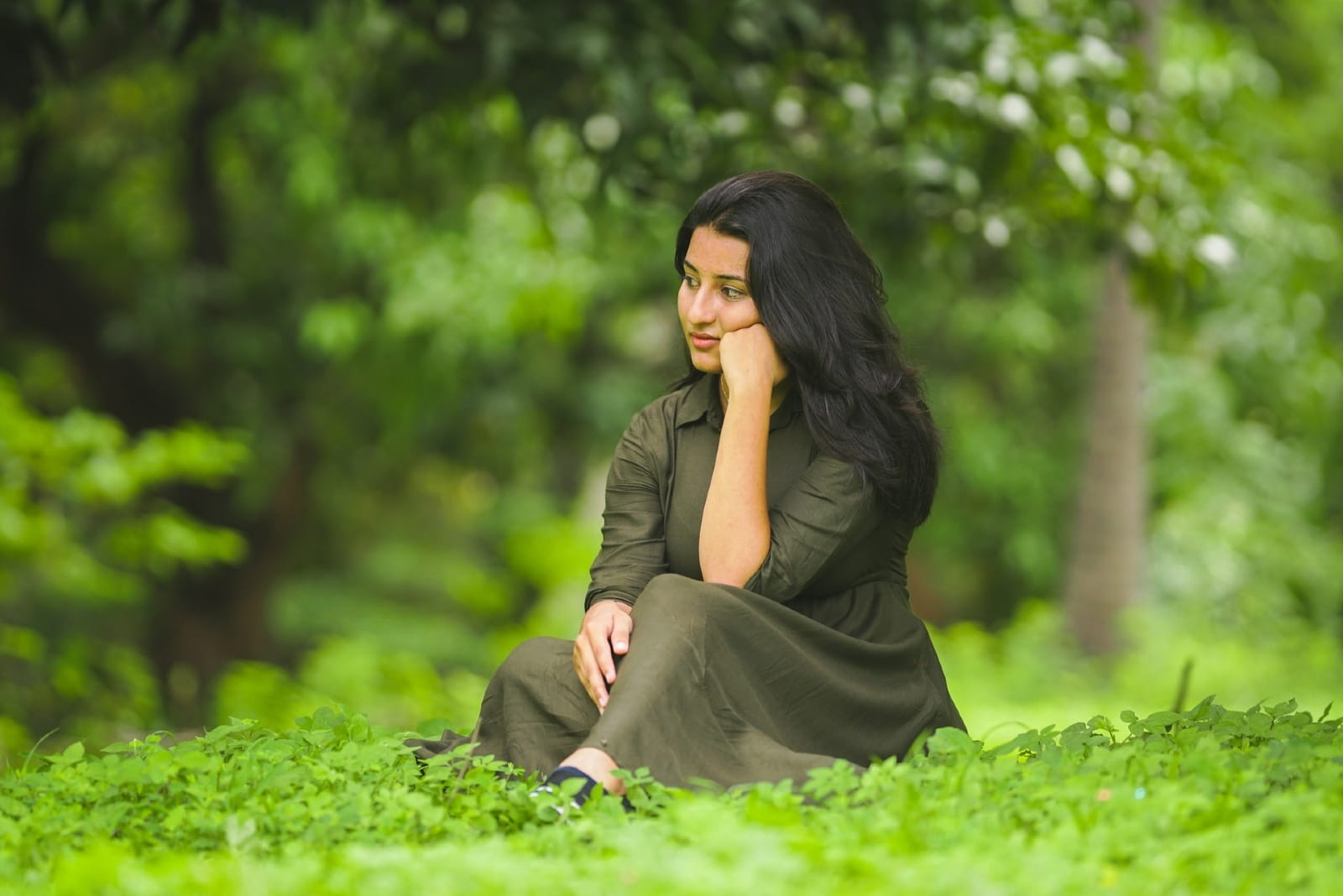 pensive woman in green dress sitting on grass