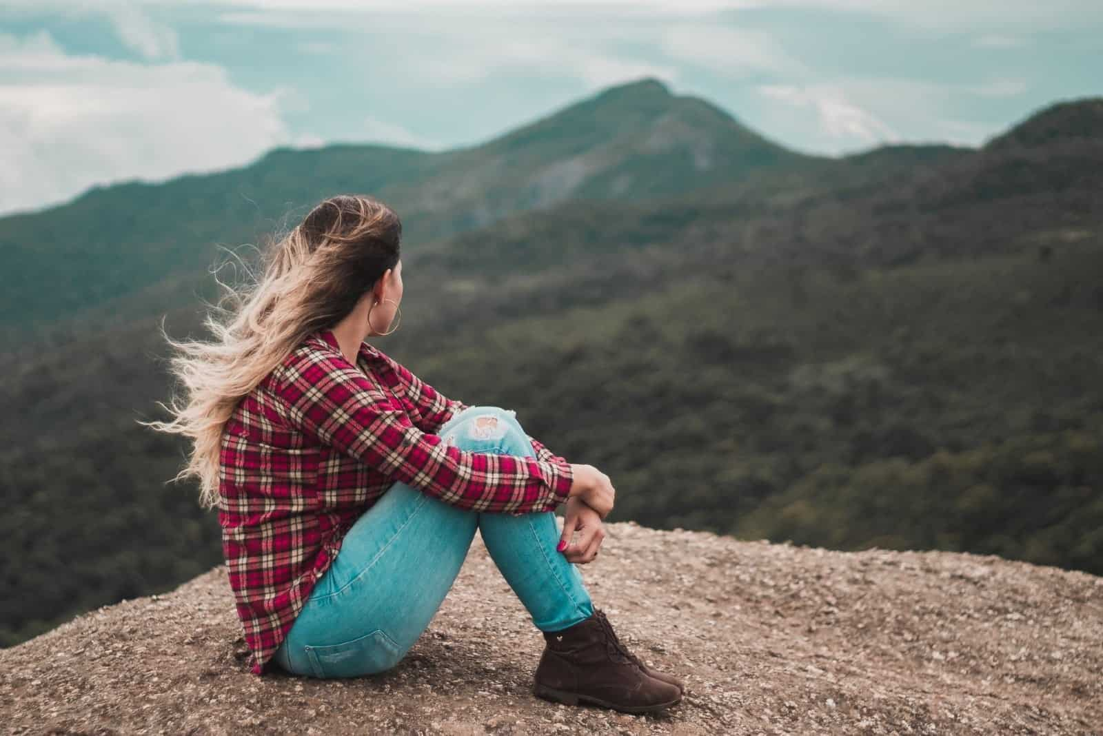 woman sitting on ground looking at mountain