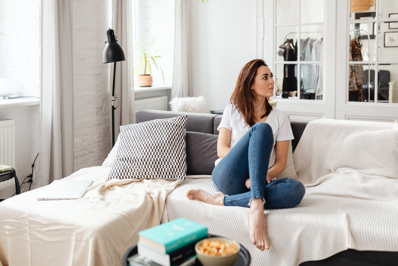 pensive woman in white t-shirt sitting on sofa