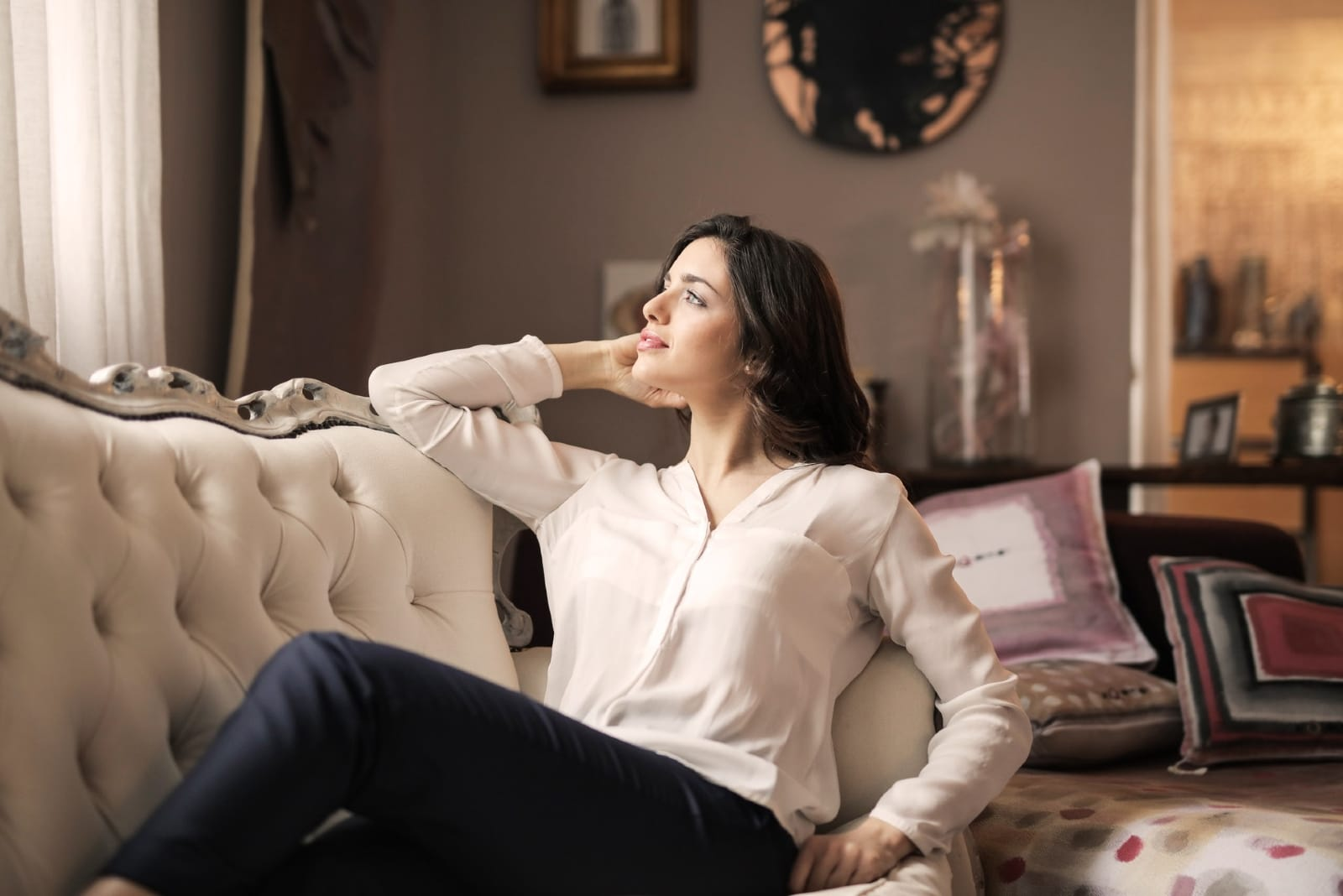 woman in white shirt sitting on sofa