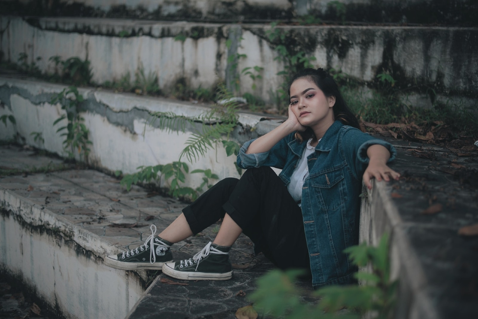 woman in denim jacket sitting on stairs