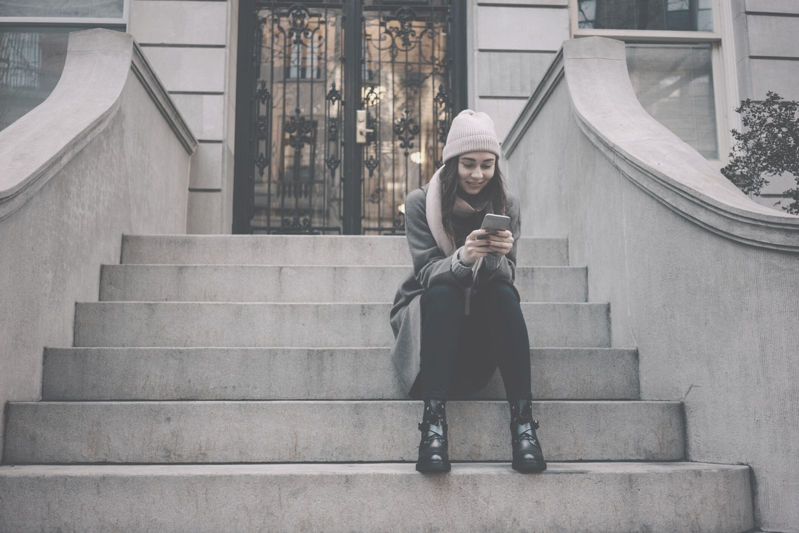 woman sitting on the stairs outside a building and texting on phone
