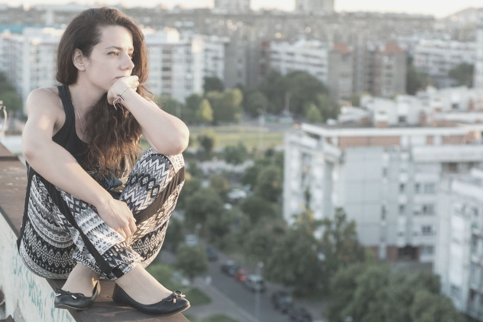 woman sitting on top of the ledge of the building thinking deeply