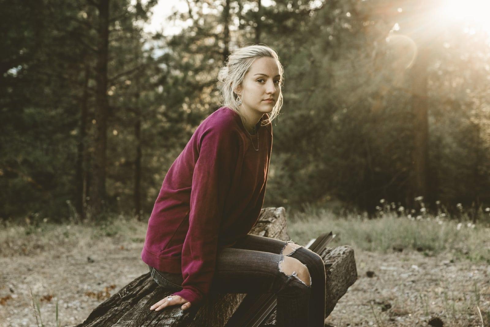 blonde woman in burgundy sweatshirt sitting on wood log