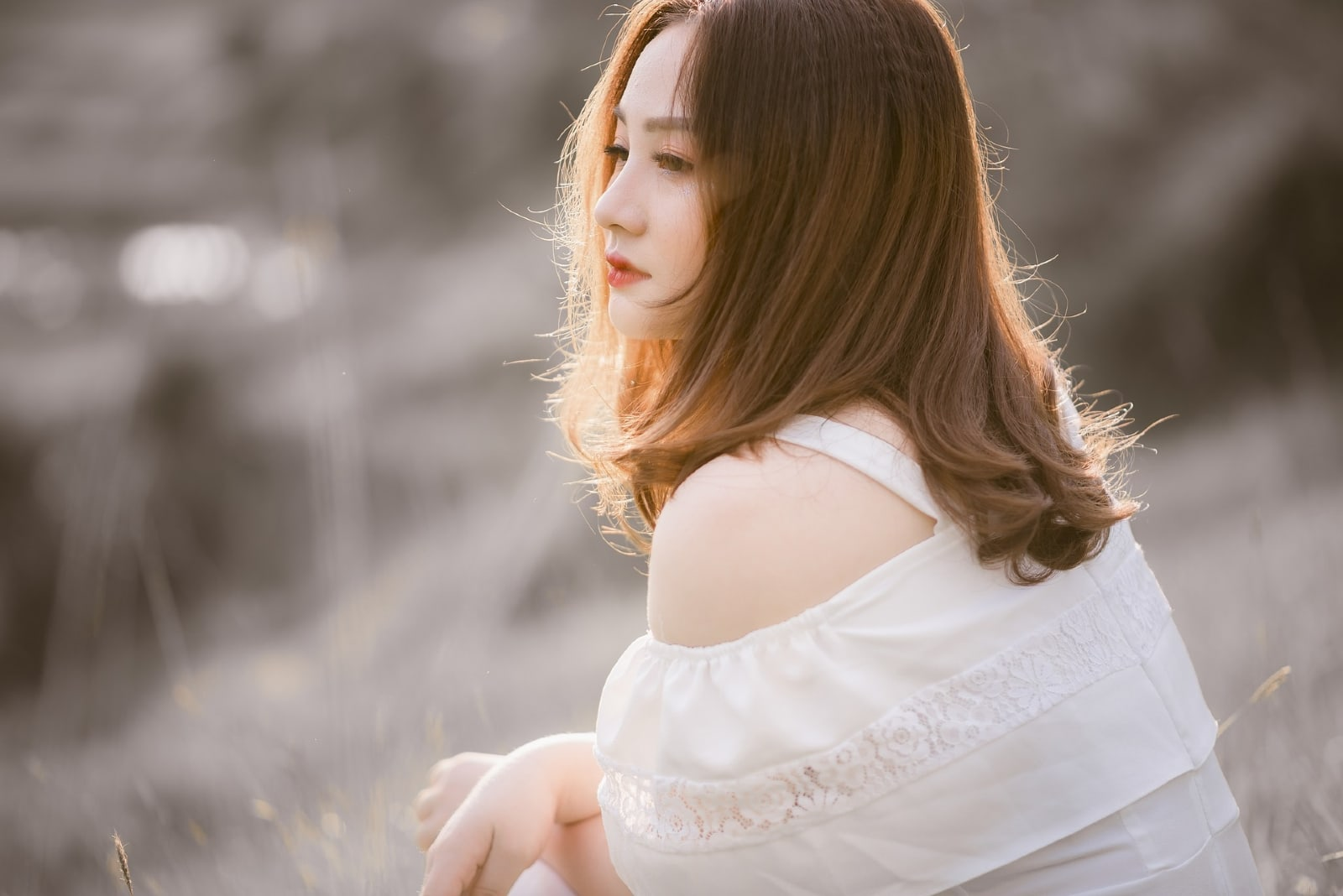 sad woman in white top sitting outdoor