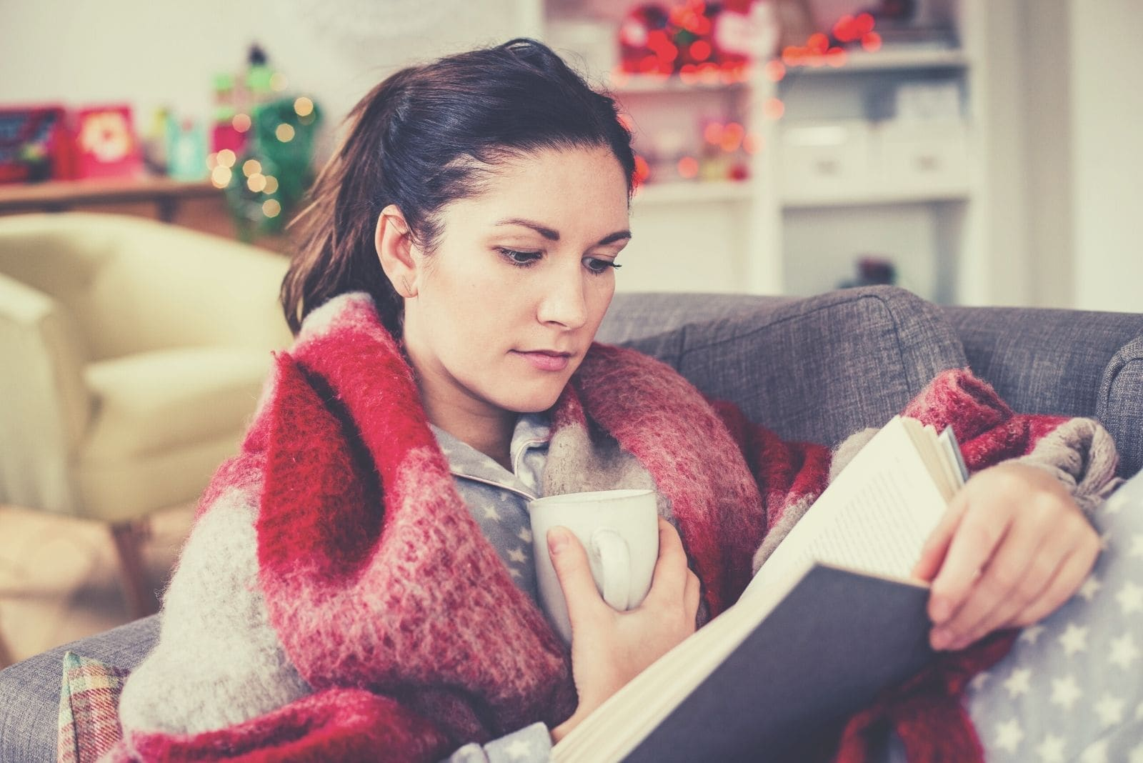 woman sitting with her feet up on a sofa relaxing with a book and coffee