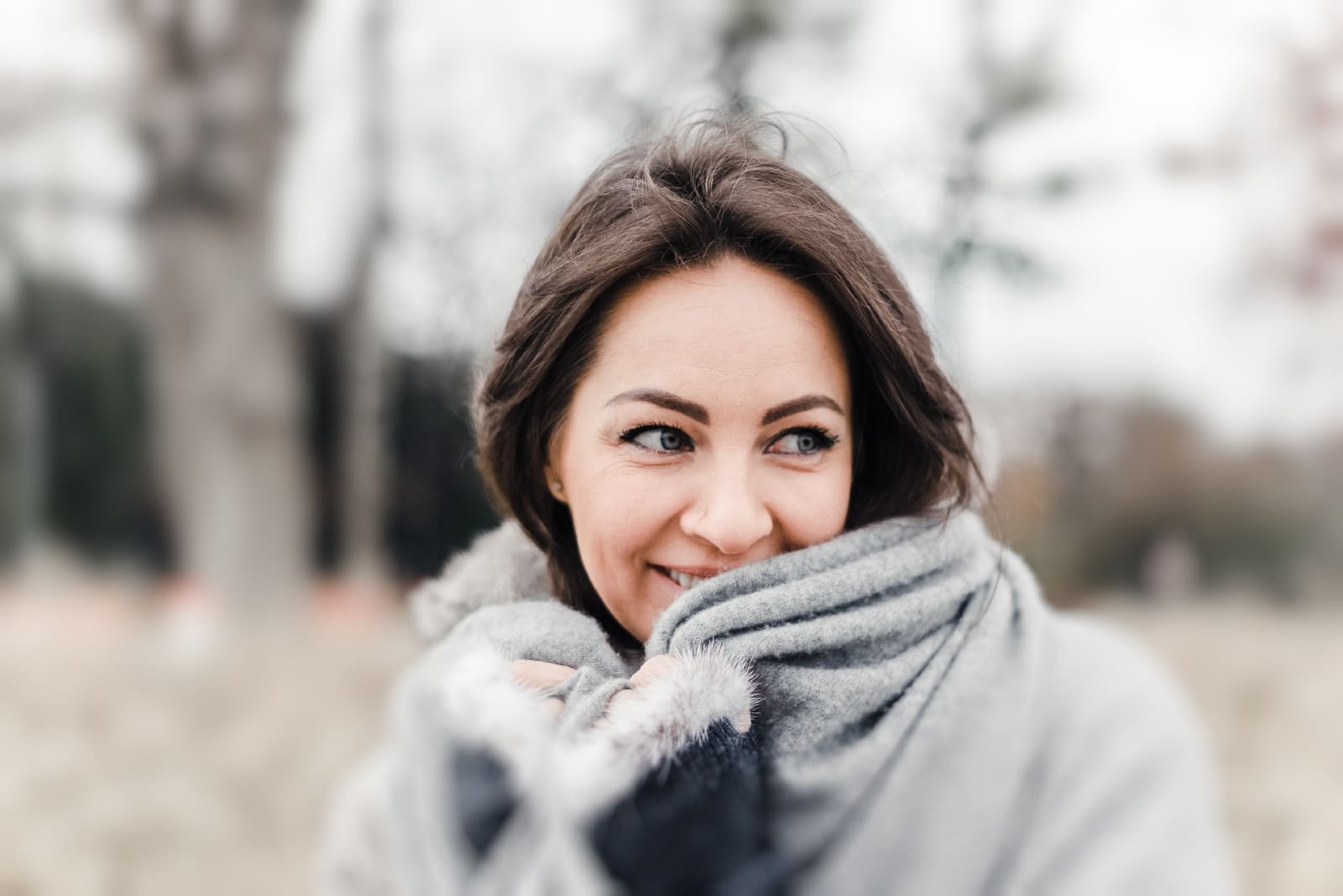 woman in gray coat smiling while standing outdoor