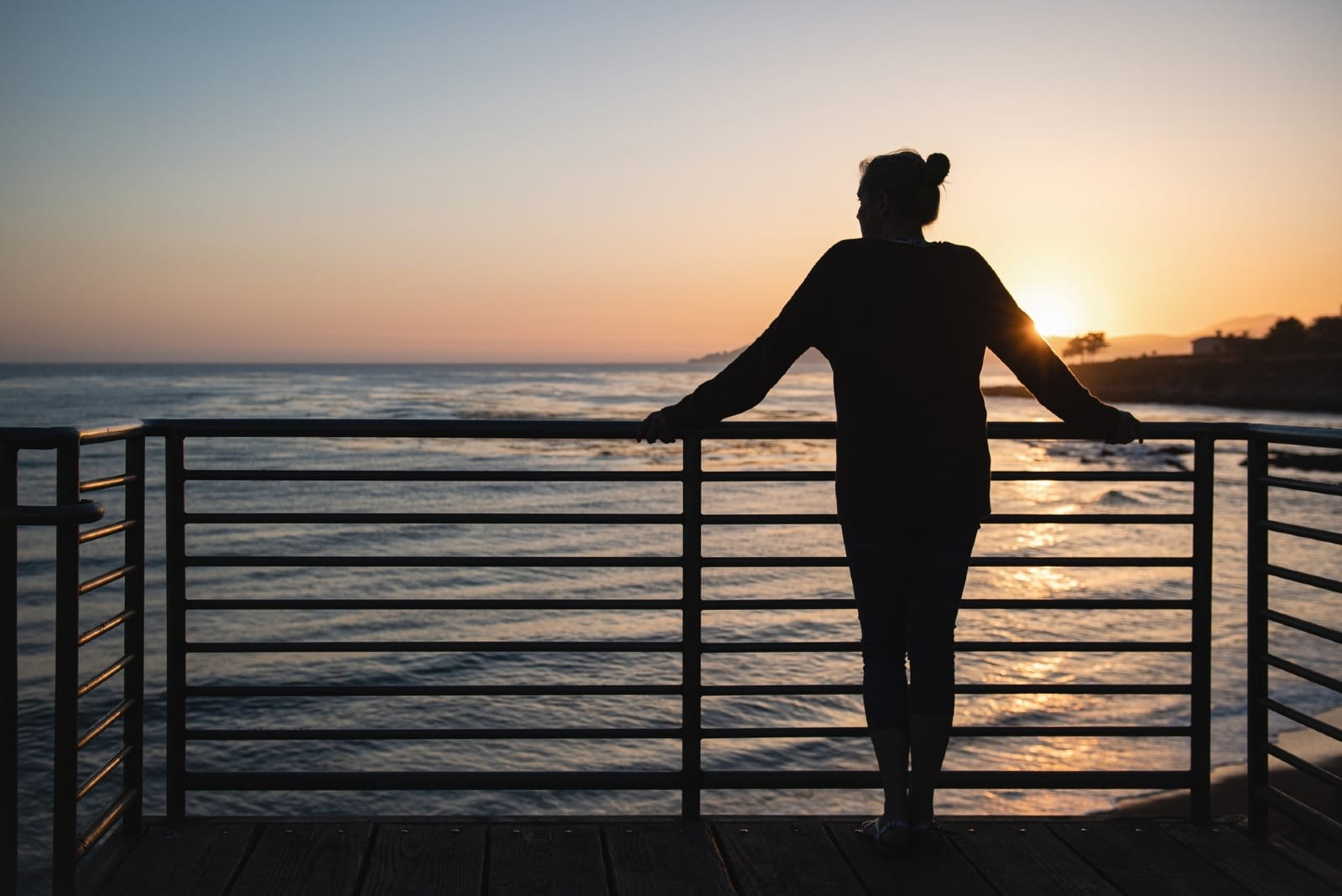 woman standing by the railing during sunset