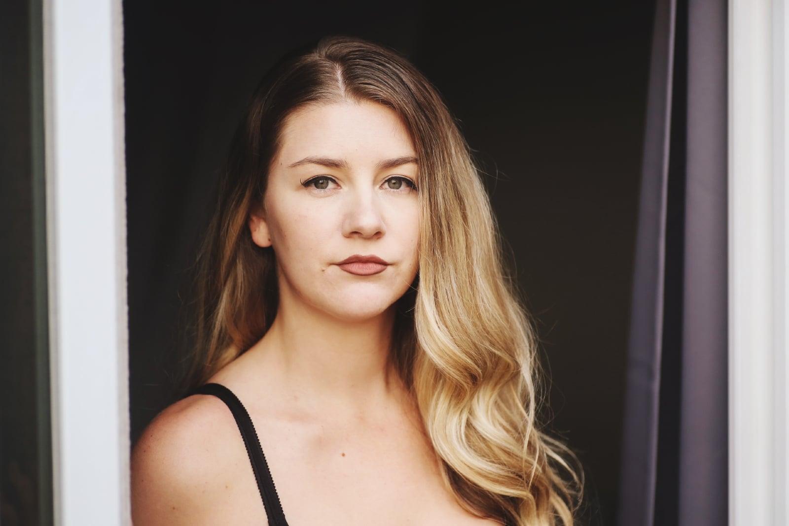 blonde woman in black top standing near door