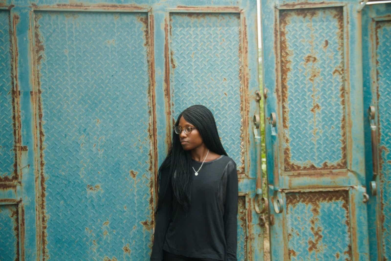 sad woman in black sweatshirt standing near door