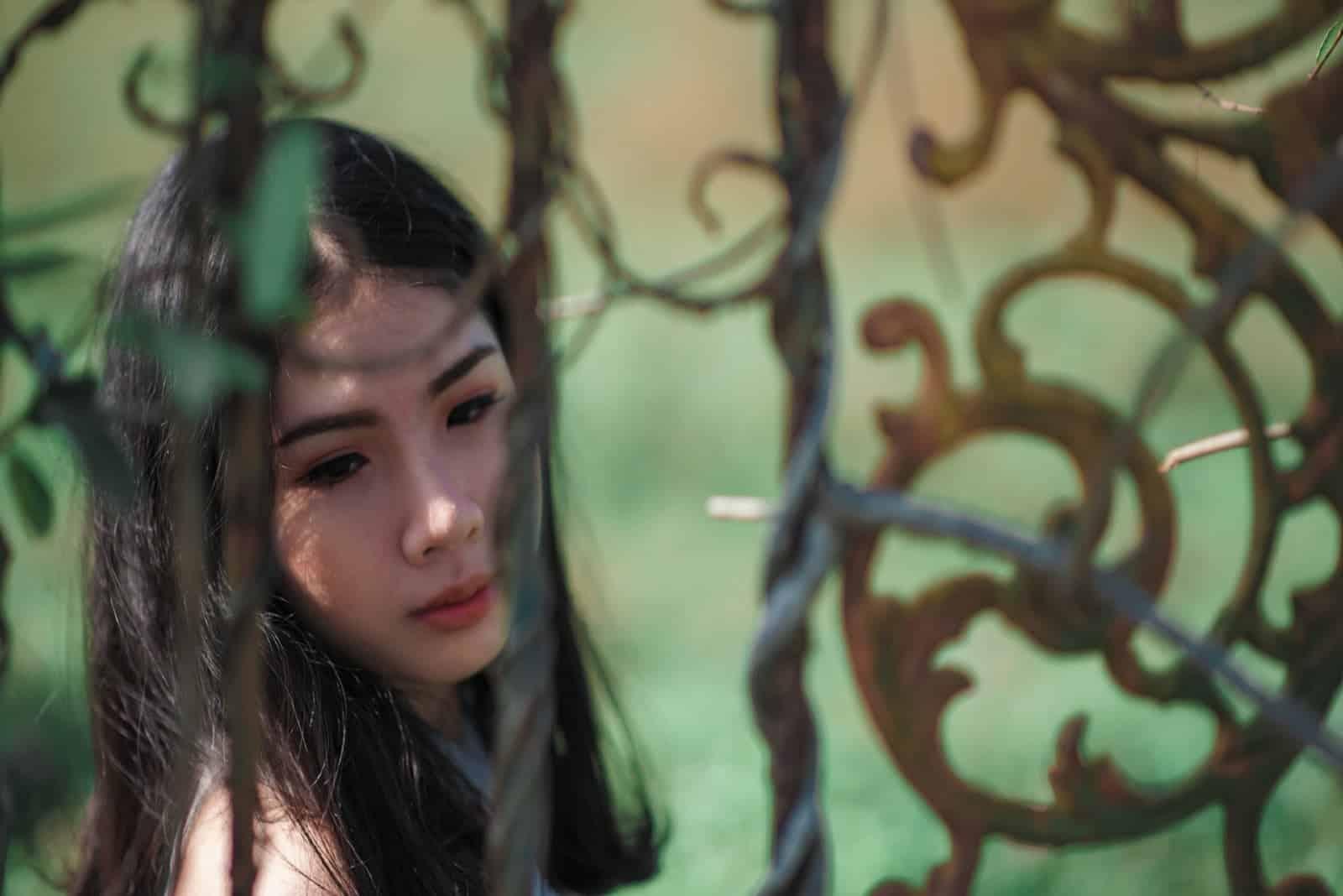 sad woman standing near black metal gate