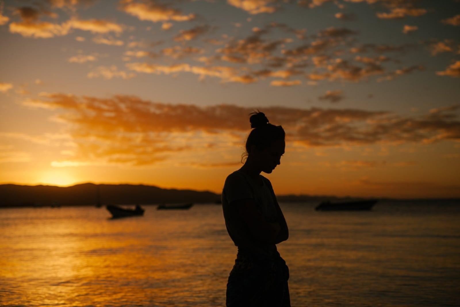 sad woman standing near sea during sunset