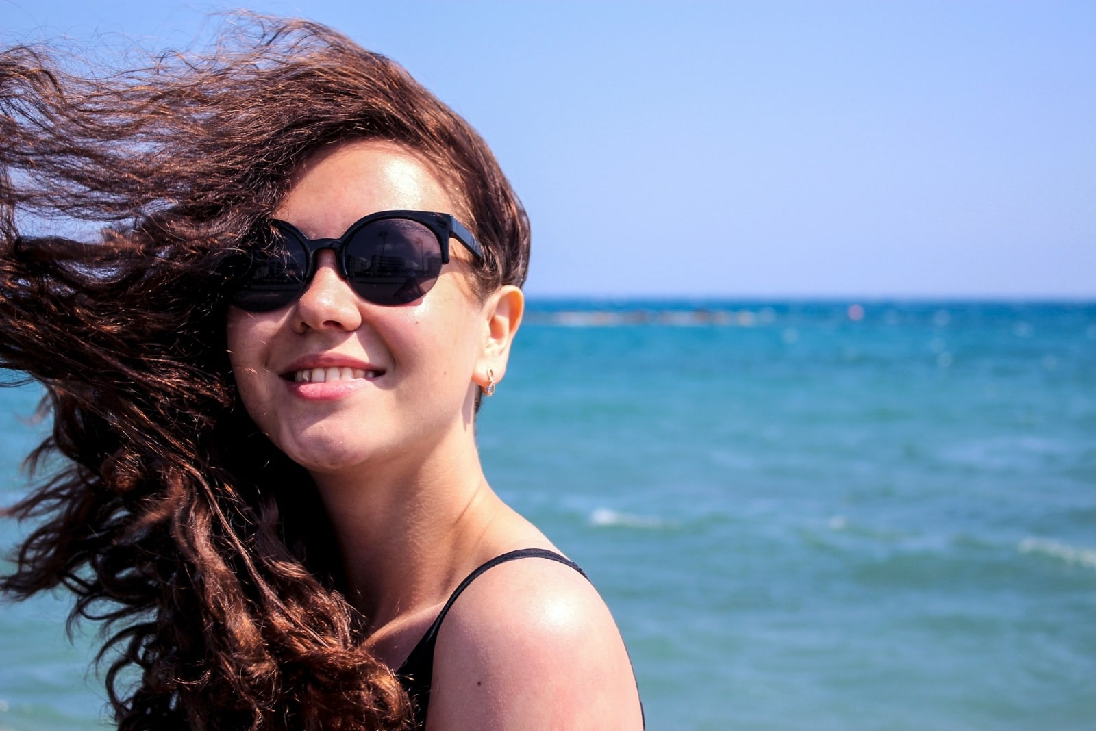 woman with sunglasses standing near sea