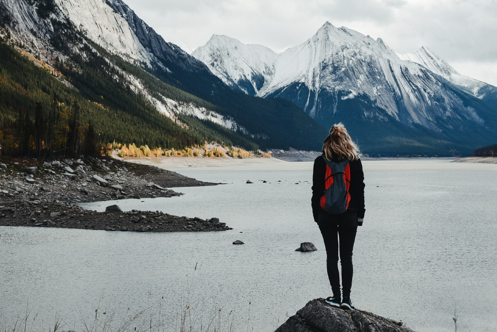 woman with backpack standing on rock looking at mountain