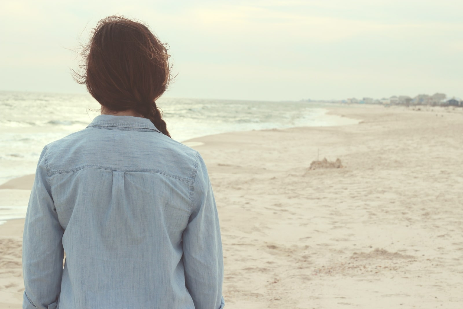 woman in denim shirt standing on shore looking at ocean