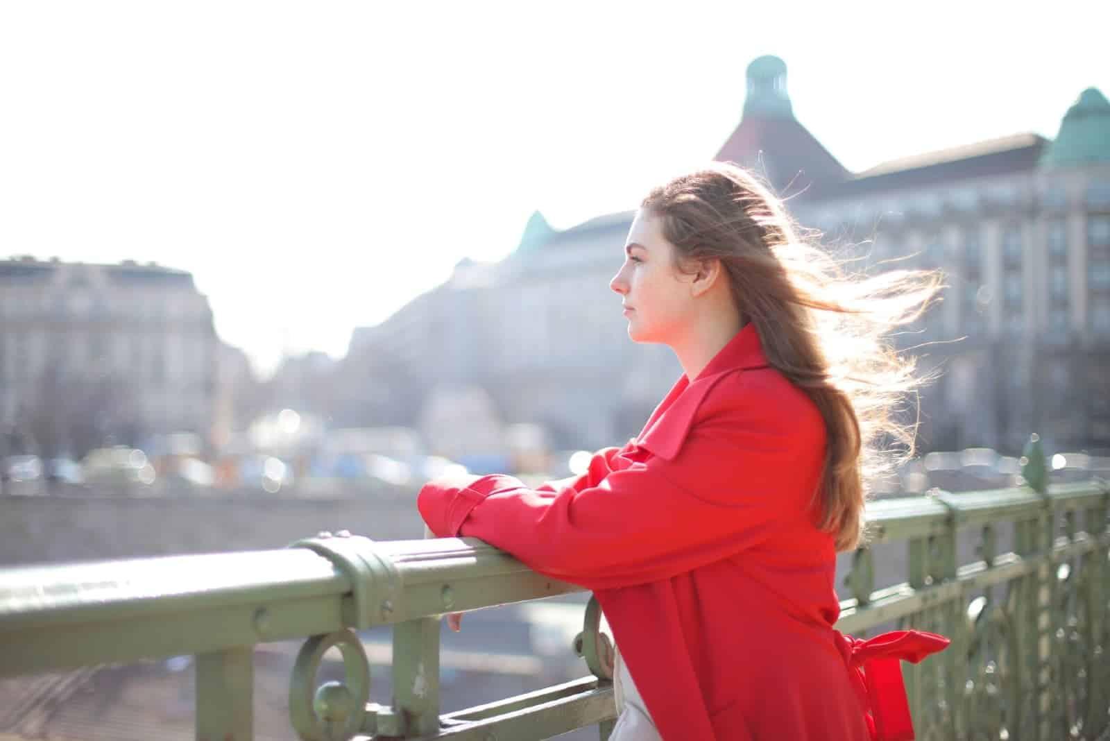 woman in red coat standing on the bridge