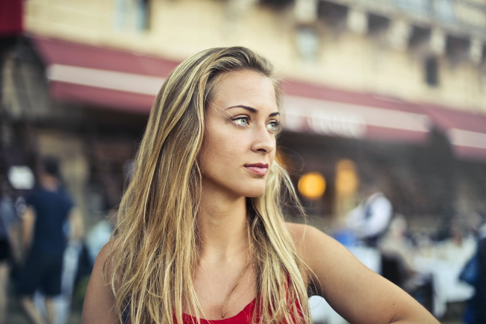 blonde woman in red top standing on the street