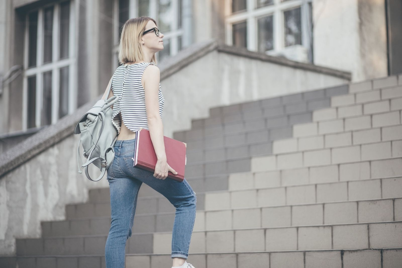 woman student climbing the stairs carrying books and looking hopeful