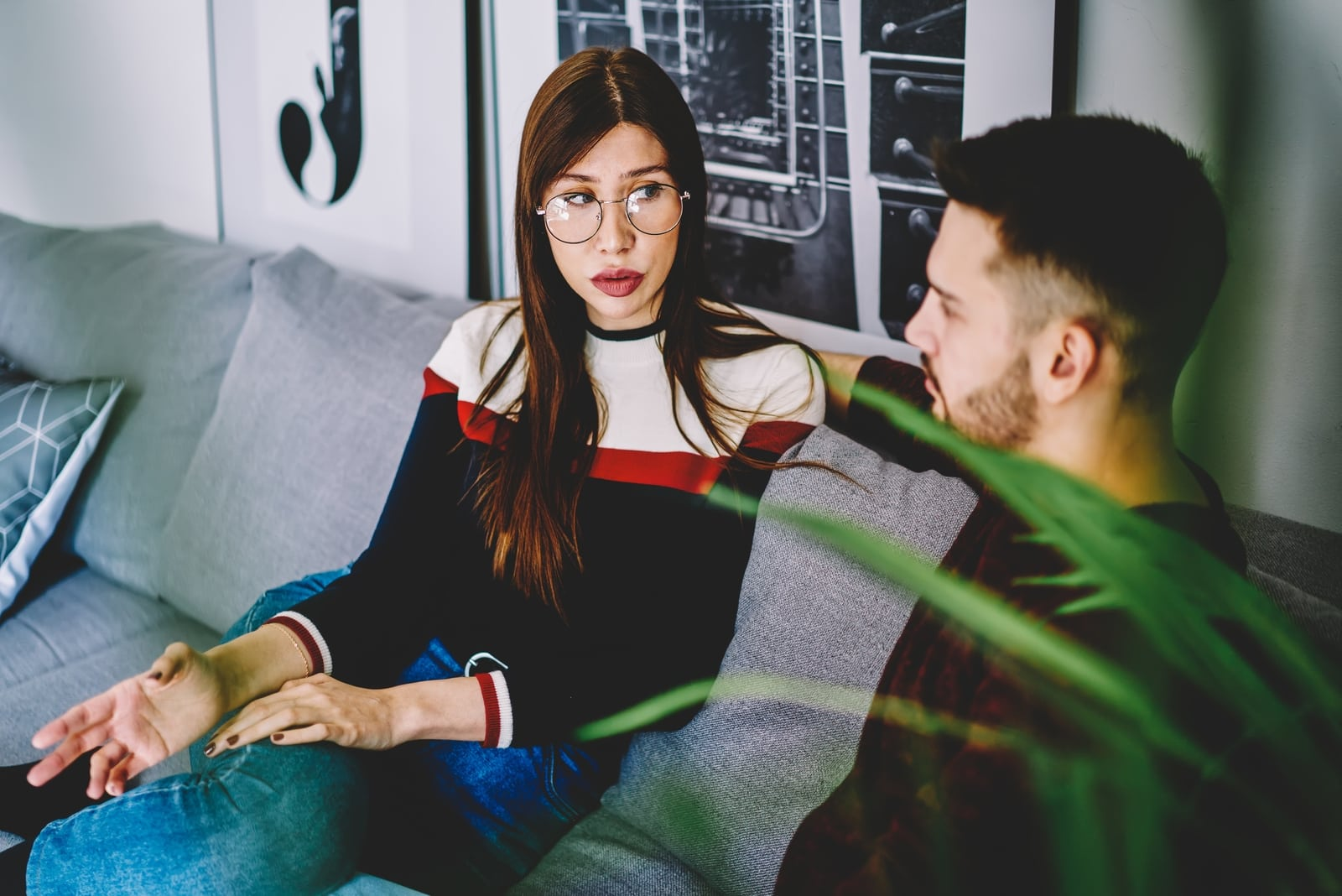 woman with eyeglasses talking to man while sitting on sofa