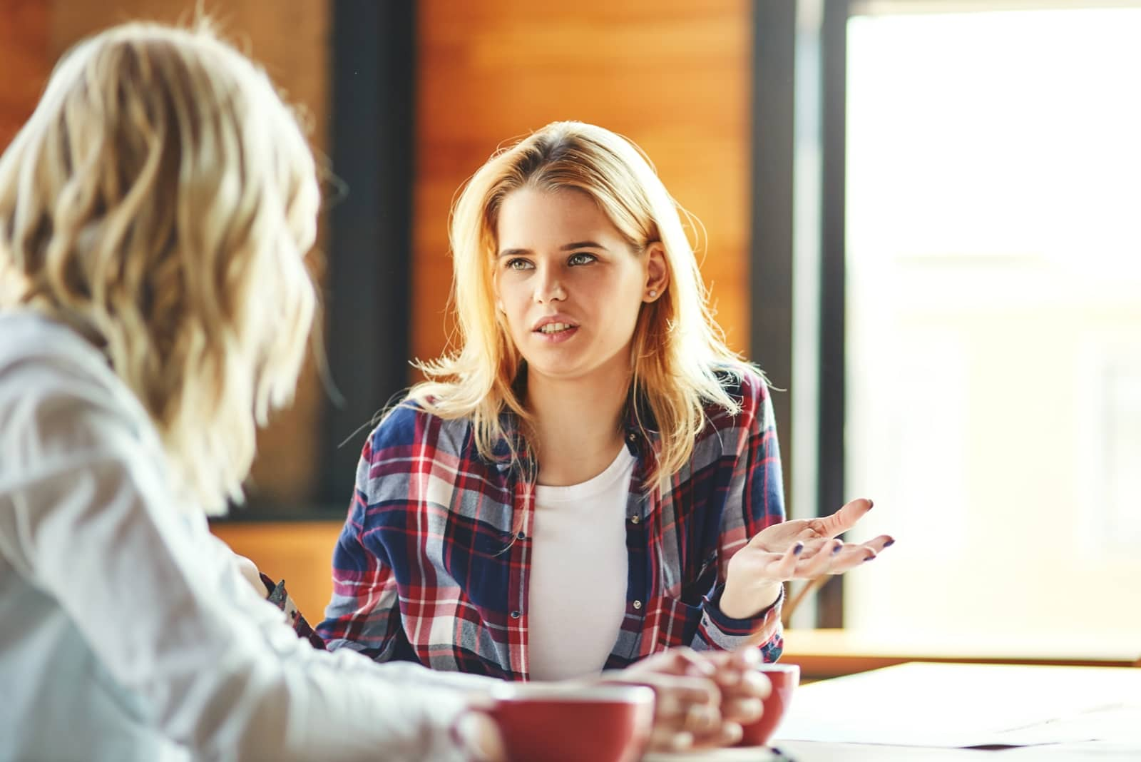 woman talking to woman while sitting at table